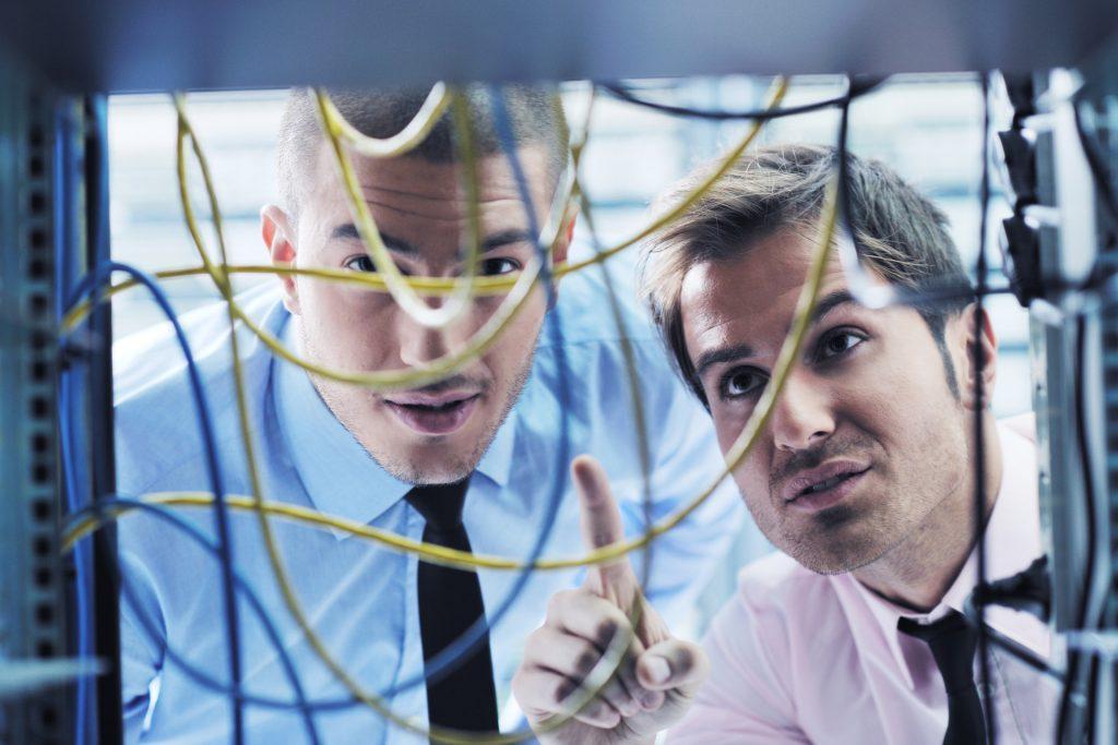 Två män som tittar på nätverkskablar
