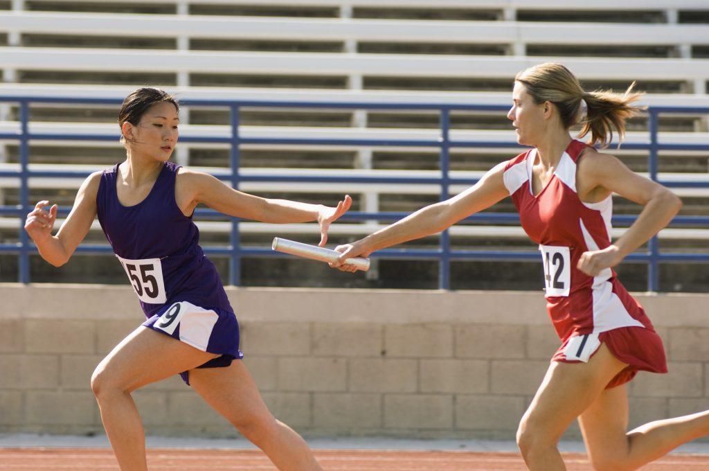 Kvinnliga löperskor med stafettpinne